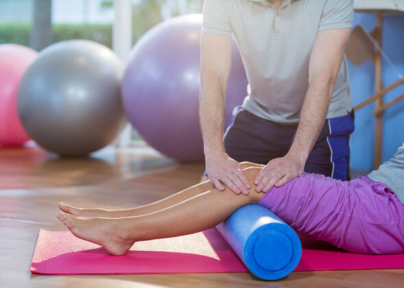 Physiotherapist+assisting+woman+while+exercising+on+exercise+mat